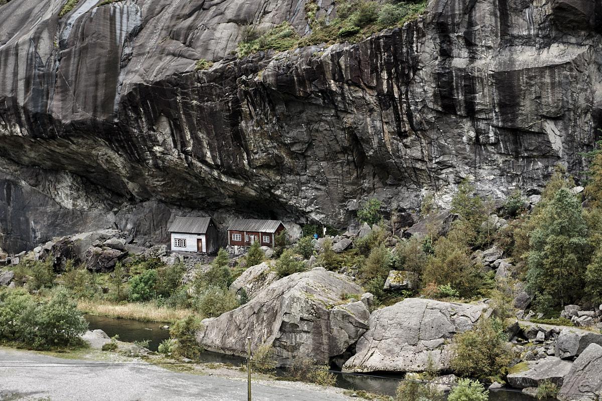 Kleine Häuschen ducken sich unter die riesige Steinwand.