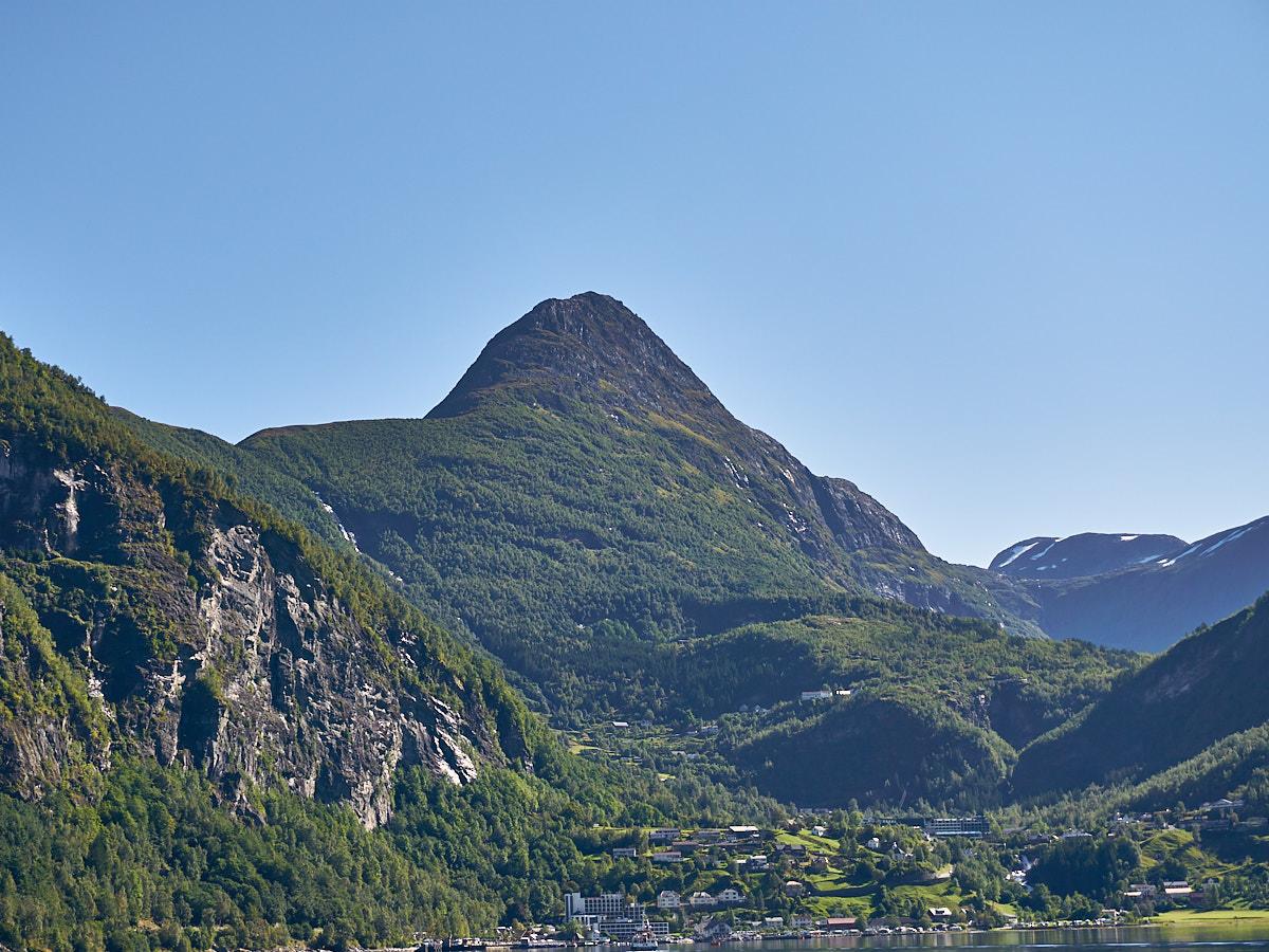 Die Stadt Geiranger kommt, umgeben von hohen Bergen, wieder in Sicht.