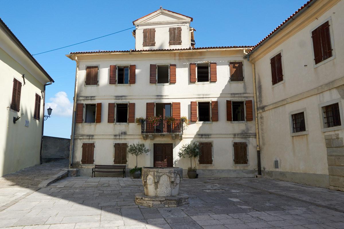 Romanischer kommunaler Palast mit Brunnen und dem Wappen der Stadt