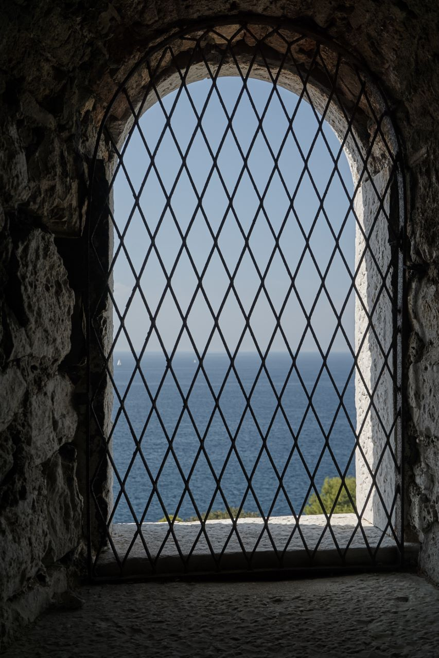 vergittertes Fenster mit Blick auf das Meer